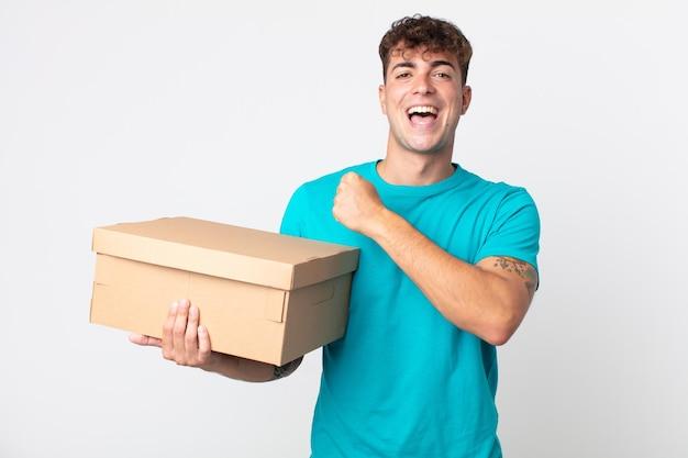 Giovane bell'uomo che si sente felice e affronta una sfida o festeggia e tiene in mano una scatola di cartone