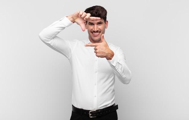 Giovane uomo bello sentirsi felice, amichevole e positivo, sorridente e facendo un ritratto o una cornice con le mani