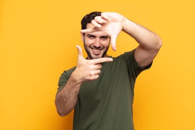 Giovane uomo bello sentirsi felice, amichevole e positivo, sorridente e fare un ritratto o una cornice con le mani