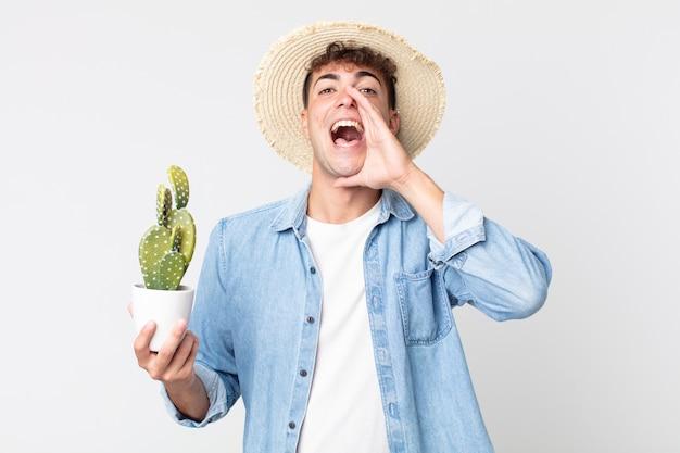 Giovane uomo bello sentirsi felice, dando un grande grido con le mani vicino alla bocca. contadino con in mano un cactus decorativo