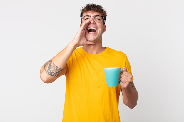 Giovane bell'uomo che si sente felice, fa un grande grido con le mani vicino alla bocca e tiene una tazza di caffè