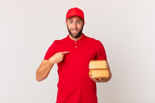 Giovane bell'uomo che si sente felice e indica se stesso con un hamburger eccitato che consegna il concetto