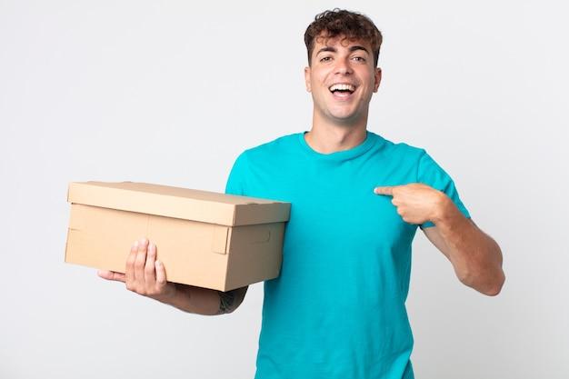 Giovane bell'uomo che si sente felice e indica se stesso con un eccitato e tiene in mano una scatola di cartone