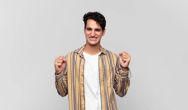 Giovane uomo bello che si sente felice, positivo e di successo, celebra la vittoria, i risultati o la buona fortuna