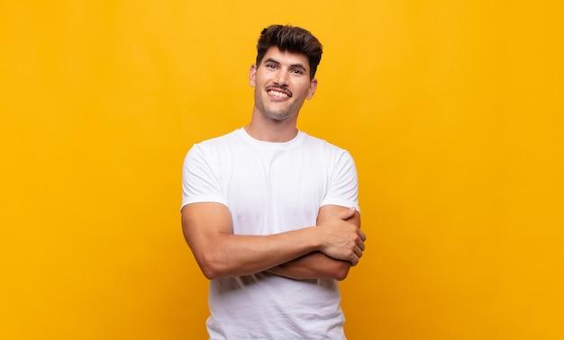 Giovane uomo bello che si sente felice, orgoglioso e speranzoso, chiedendosi o pensando, alzando lo sguardo per copiare lo spazio con le braccia incrociate