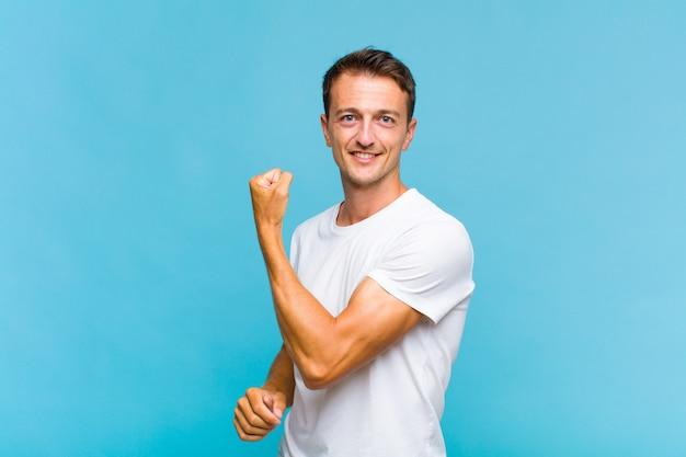 Giovane uomo bello sentirsi felice, soddisfatto e potente, flettendo in forma e bicipiti muscolosi, cercando forte dopo la palestra
