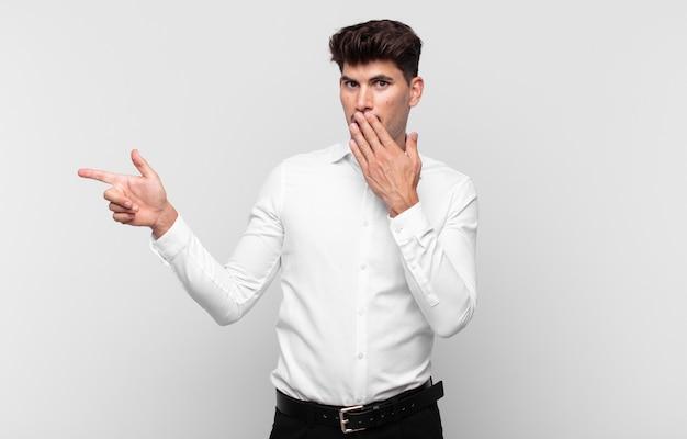 Giovane uomo bello che si sente felice, scioccato e sorpreso, coprendo la bocca con la mano e indicando lo spazio laterale della copia