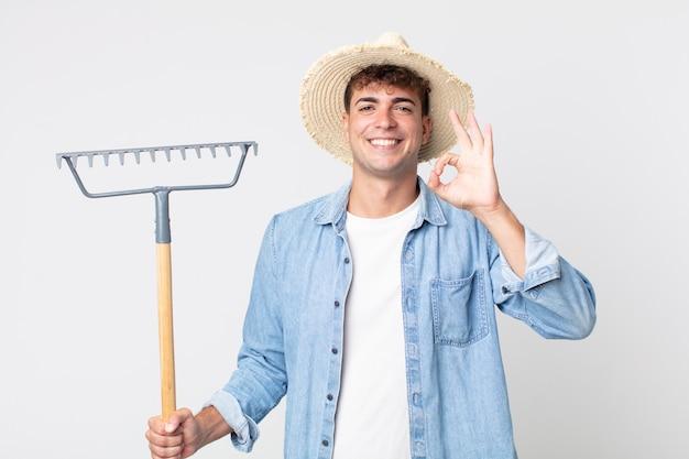 Giovane bell'uomo che si sente felice, mostra approvazione con un gesto ok. concetto di contadino