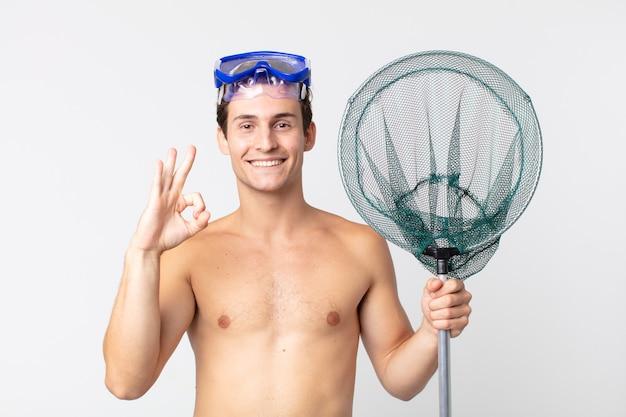 Giovane bell'uomo che si sente felice, mostra approvazione con un gesto ok con occhiali e una rete da pesca