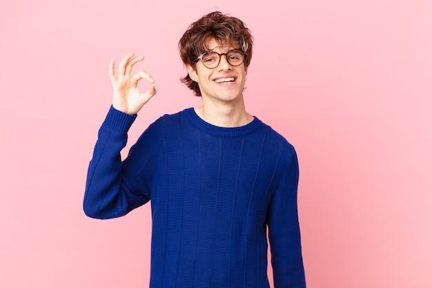 Giovane bell'uomo che si sente felice, mostra approvazione con un gesto ok