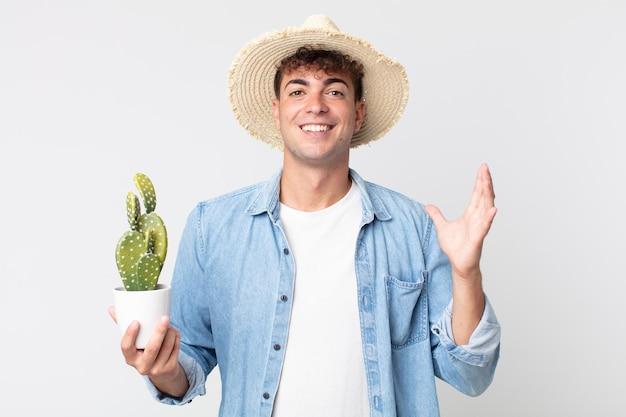 Giovane uomo bello sentirsi felice, sorpreso di realizzare una soluzione o un'idea. contadino con in mano un cactus decorativo
