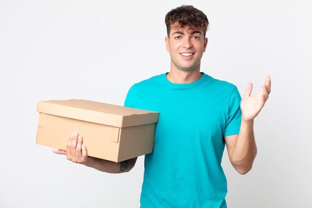 Giovane bell'uomo che si sente felice, sorpreso di realizzare una soluzione o un'idea e con in mano una scatola di cartone