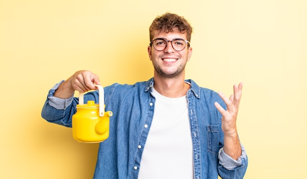 Giovane uomo bello sentirsi felice, sorpreso di realizzare una soluzione o un'idea.concetto di teiera