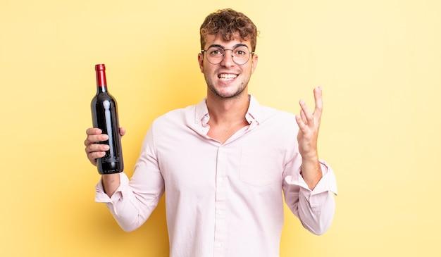 Giovane uomo bello sentirsi felice, sorpreso di realizzare una soluzione o un'idea. concetto di bottiglia di vino