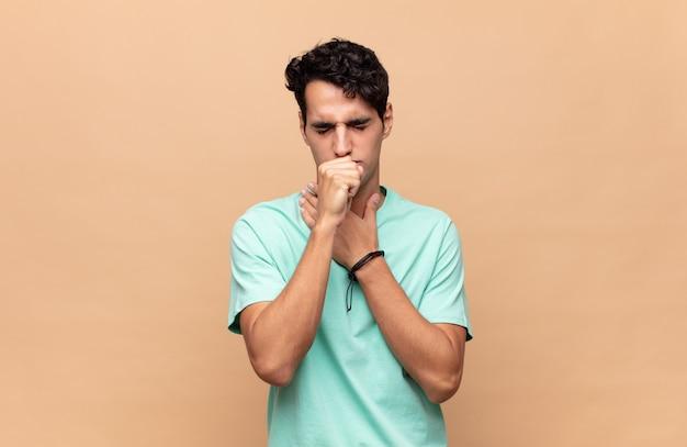 Giovane uomo bello che si sente male con mal di gola e sintomi influenzali, tosse con la bocca coperta