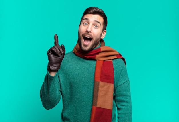 Giovane bell'uomo che si sente un genio felice ed eccitato dopo aver realizzato un'idea, alzando allegramente il dito, eureka!. concetto di freddo e inverno
