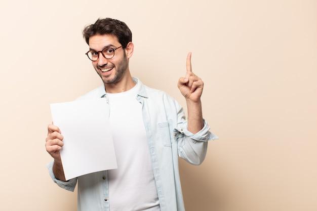 Giovane bell'uomo che si sente come un genio felice ed eccitato dopo aver realizzato un'idea, alzando allegramente il dito, eureka!