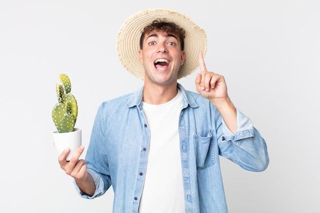 Giovane bell'uomo che si sente un genio felice ed eccitato dopo aver realizzato un'idea. contadino con in mano un cactus decorativo