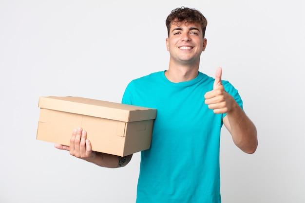 Giovane bell'uomo che si sente orgoglioso, sorride positivamente con i pollici in su e tiene in mano una scatola di cartone