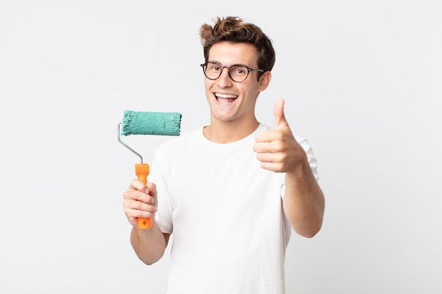Giovane bell'uomo che si sente orgoglioso, sorride positivamente con i pollici in su e tiene in mano una vernice a rullo