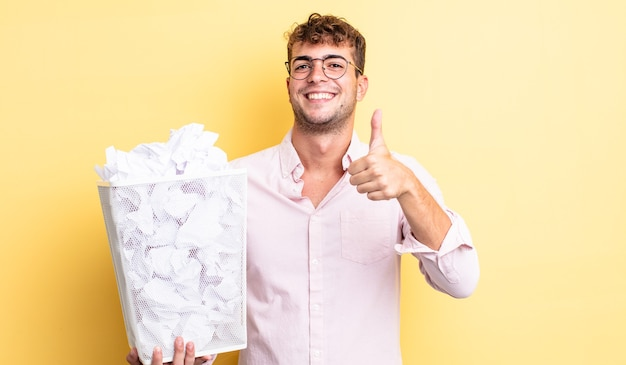 Giovane bell'uomo che si sente orgoglioso, sorride positivamente con i pollici in su. concetto di spazzatura delle palle di carta
