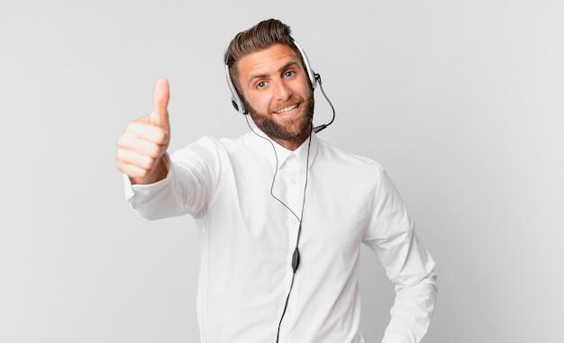 Giovane bell'uomo che si sente orgoglioso, sorride positivamente con i pollici in su. concetto di telemarketing