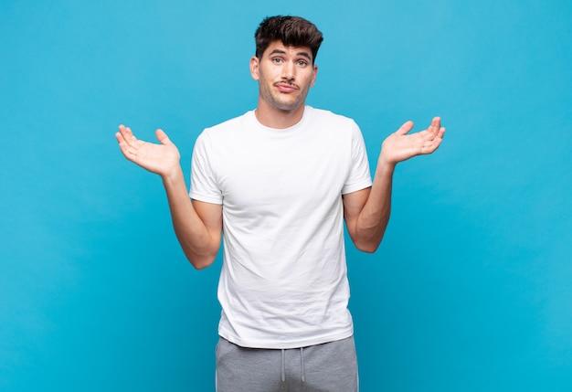 Giovane uomo bello sentirsi perplesso e confuso, dubitare, ponderare o scegliere diverse opzioni con un'espressione divertente