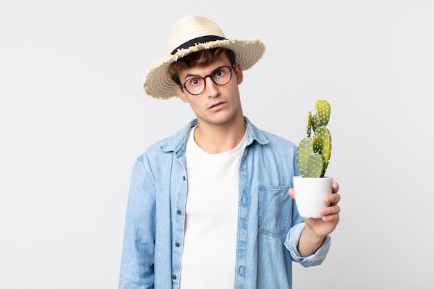 Giovane uomo bello sentirsi perplesso e confuso. contadino con in mano un cactus decorativo