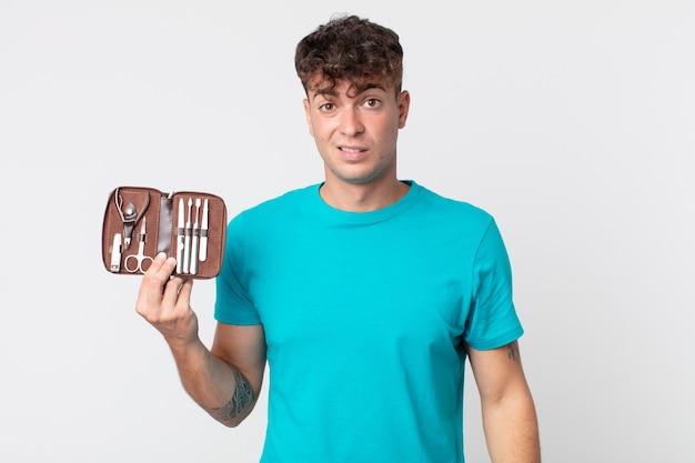 Giovane bell'uomo che si sente perplesso e confuso e tiene in mano una valigetta per attrezzi per unghie