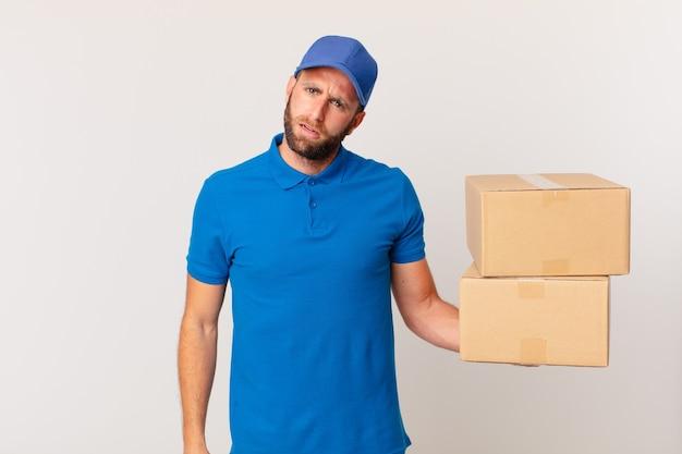 Giovane uomo bello sentirsi perplesso e confuso. concetto di consegna del pacchetto