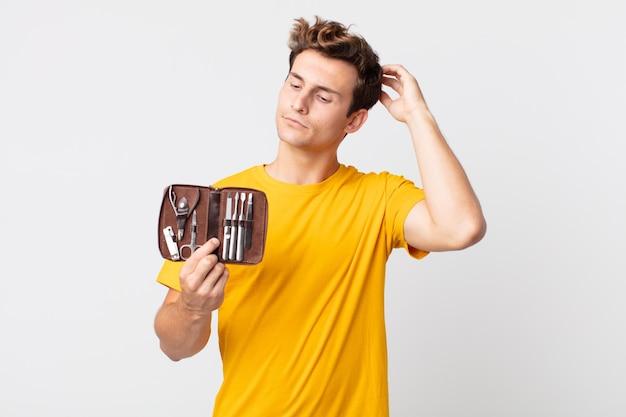 Giovane bell'uomo che si sente perplesso e confuso, si gratta la testa e tiene in mano una valigetta per attrezzi per le unghie