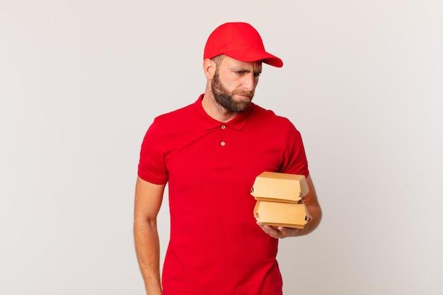 Giovane bell'uomo che si sente triste, turbato o arrabbiato e guarda l'hamburger laterale