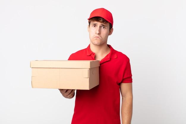 Giovane bell'uomo che si sente triste e piagnucoloso con uno sguardo infelice e piange il concetto di servizio di consegna del pacchetto.