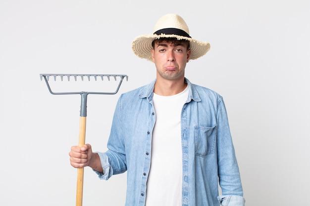 Giovane bell'uomo che si sente triste e piagnucoloso con uno sguardo infelice e piange. concetto di contadino