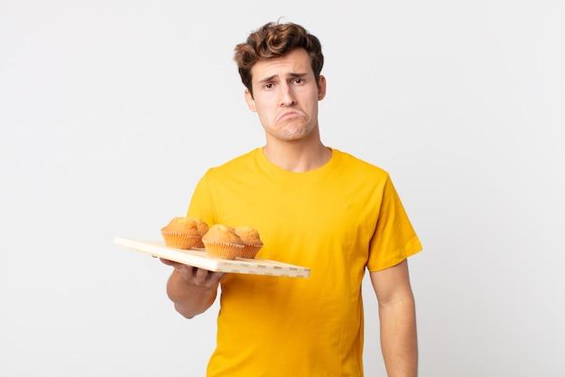 Giovane bell'uomo che si sente triste e piagnucoloso con uno sguardo infelice e piange con in mano un vassoio di muffin