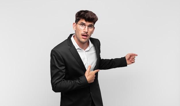 Giovane uomo bello che si sente scioccato e sorpreso, indicando lo spazio di copia sul lato con sguardo stupito e a bocca aperta