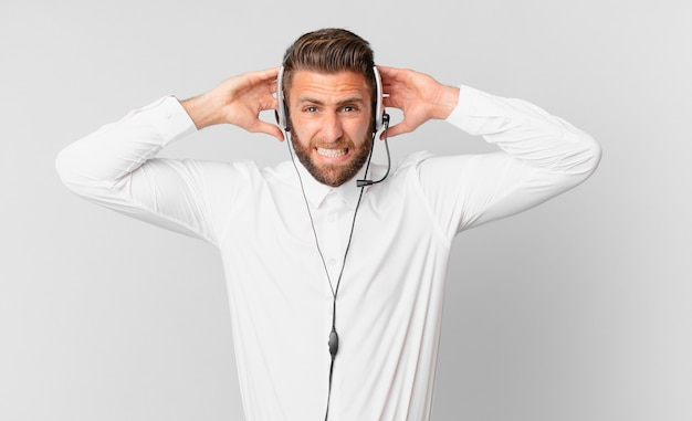 Giovane bell'uomo che si sente stressato, ansioso o spaventato, con le mani sulla testa. concetto di telemarketing