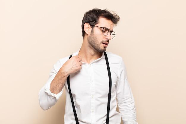 Giovane uomo bello sentirsi stressato, ansioso, stanco e frustrato, tirando il collo della camicia, sembrando frustrato dal problema