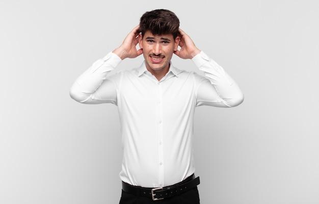 Giovane uomo bello che si sente stressato, preoccupato, ansioso o spaventato, con le mani sulla testa, in preda al panico per errore