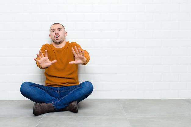 Giovane uomo bello che si sente terrorizzato, indietreggia e urla in preda all'orrore e al panico, reagendo a un incubo seduto sul pavimento