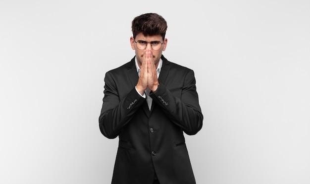 Giovane uomo bello che si sente preoccupato, fiducioso e religioso, pregando fedelmente con i palmi premuti, chiedendo perdono