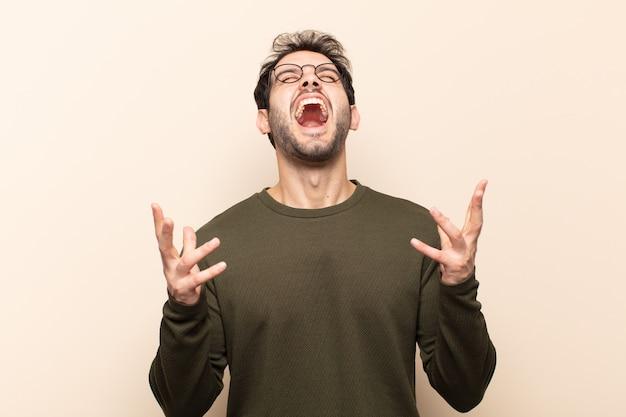 Giovane uomo bello che urla furiosamente, sentendosi stressato e infastidito con le mani in aria dicendo perché me