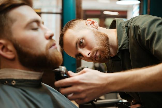 Giovane uomo bello che si fa tagliare la barba dal parrucchiere barbuto mentre è seduto in poltrona al barbiere. focus sul parrucchiere.