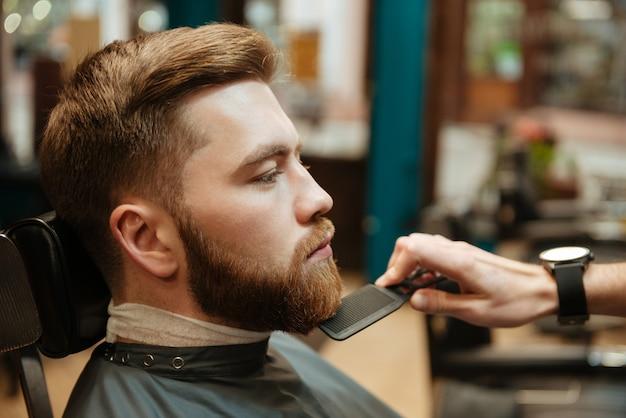 Giovane uomo bello che si fa tagliare la barba dal parrucchiere mentre è seduto in poltrona al barbiere.