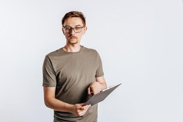 Giovane uomo bello in vetri che tengono cartella per documenti su bianco isolato