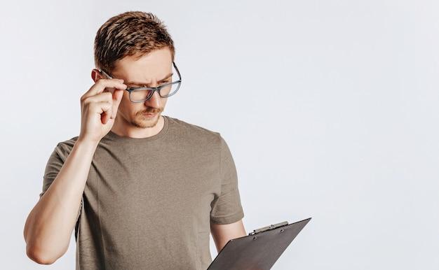 Giovane uomo bello in bicchieri tenendo la cartella su sfondo bianco isolato