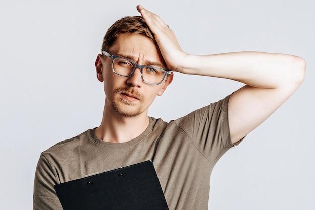 Il giovane uomo bello con gli occhiali è infelice e tiene la cartella su uno spazio bianco isolato
