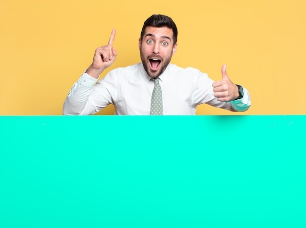 Giovane uomo bello felice e orgoglioso con cartello verde