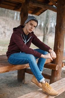 Giovane uomo bello in un cappello e stivali di pelle in una foresta