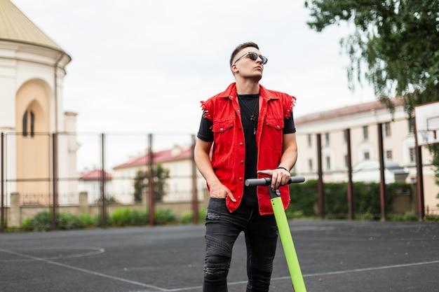Giovane hipster uomo bello in un elegante gilet di jeans rossi in jeans neri in occhiali da sole sta con uno scooter elettrico